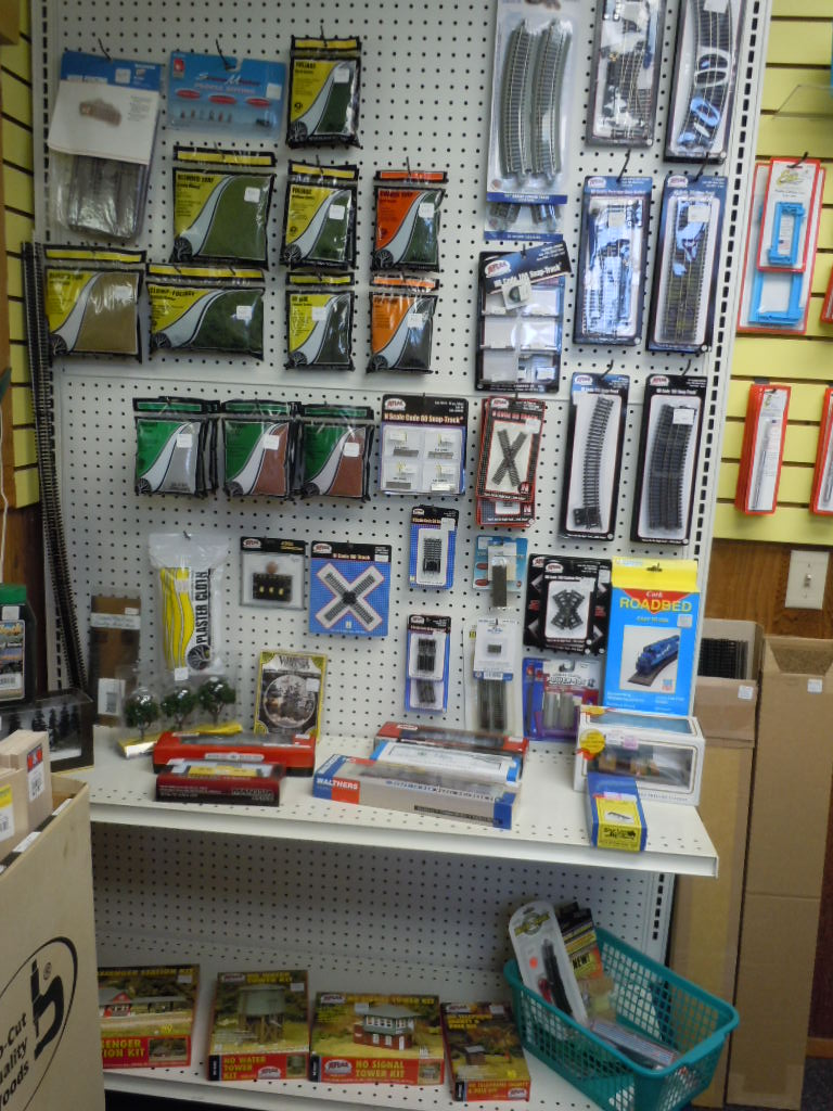 Train track, rolling stock, scenery and tools in the hobby shop